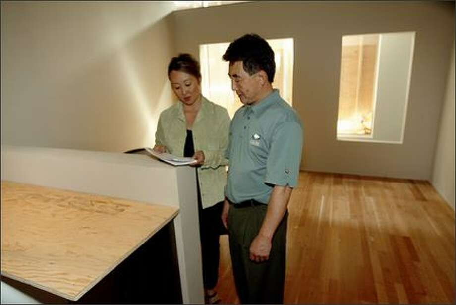 Iolanthe Chan-McCarthy of Urban Pacific Real Estate, left, and G. David Hoy, president of HMI Real Estate Inc., in a 300-square-foot unfinished condo. Studios that size range from $149,950 to $245,950. Photo: Grant M. Haller, Seattle Post-Intelligencer / Seattle Post-Intelligencer