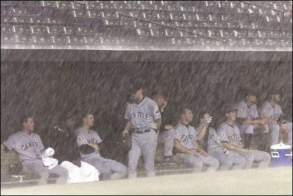 The Mariners wait in the visitors' dugout at Camden Yards after a torrential downpour interrupts the ninth inning Friday night. The M's were trailing 0-3 with two outs on the board when the rain began.