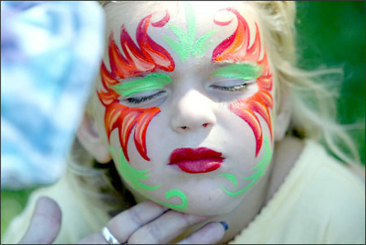 Isabelle Ellenthal of Seattle has her face painted by Irina Filatova of New Orleans.