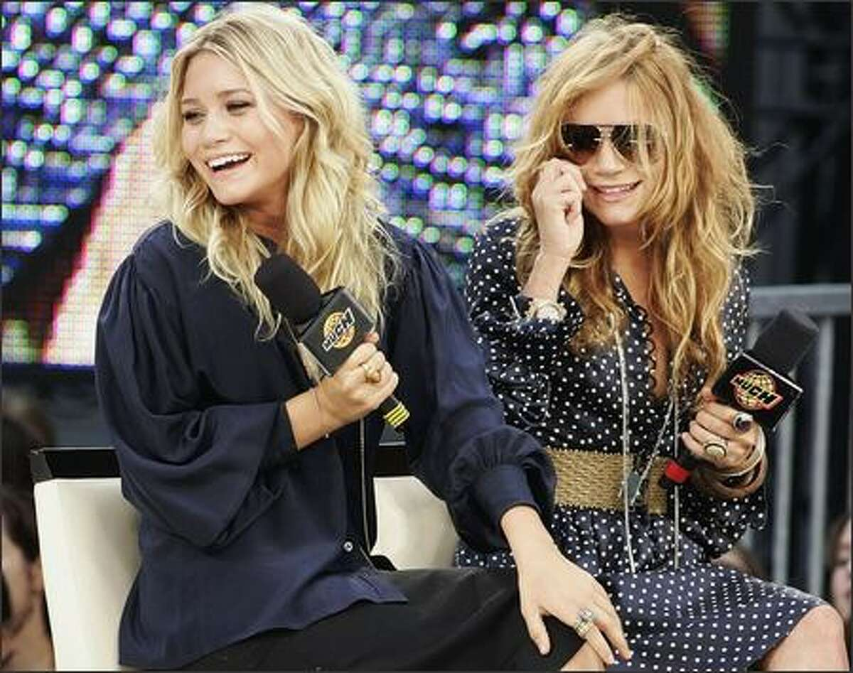 """The empire otherwise known as Ashley, left, and Mary-Kate Olsen were in Toronto on Tuesday to launch the new fall collection of their fashion line -- called, what else? -- the mary-kateandashley brand. During a break from the live show """"Much Music,"""" they signed autographs for their fans and their target market, teenage girls. In the U.S., the twins' clothes are sold at Wal-Mart."""