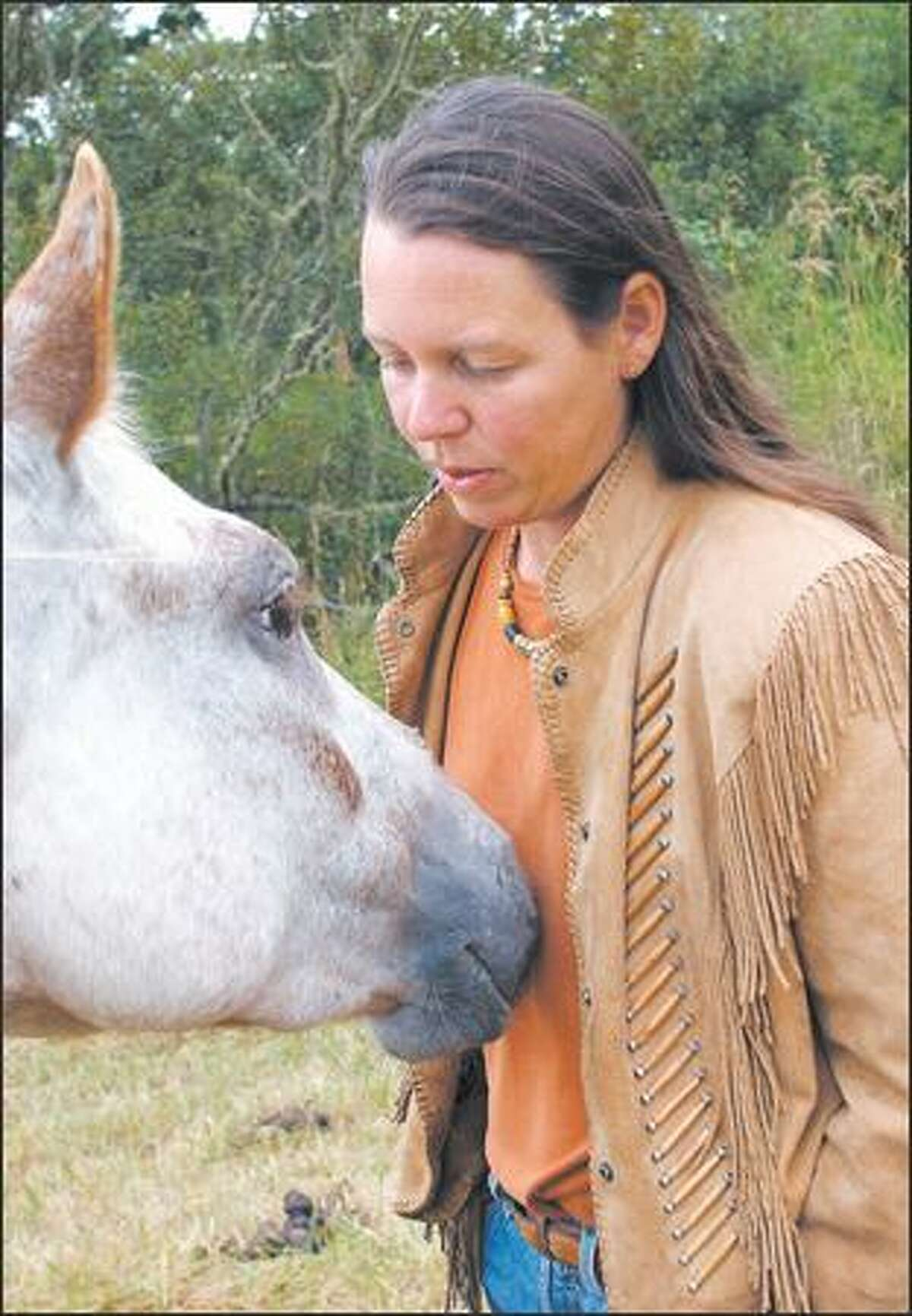 First-time novelist Karen Fisher greets one of her nine horses at her 10-acre family home on Lopez Island.
