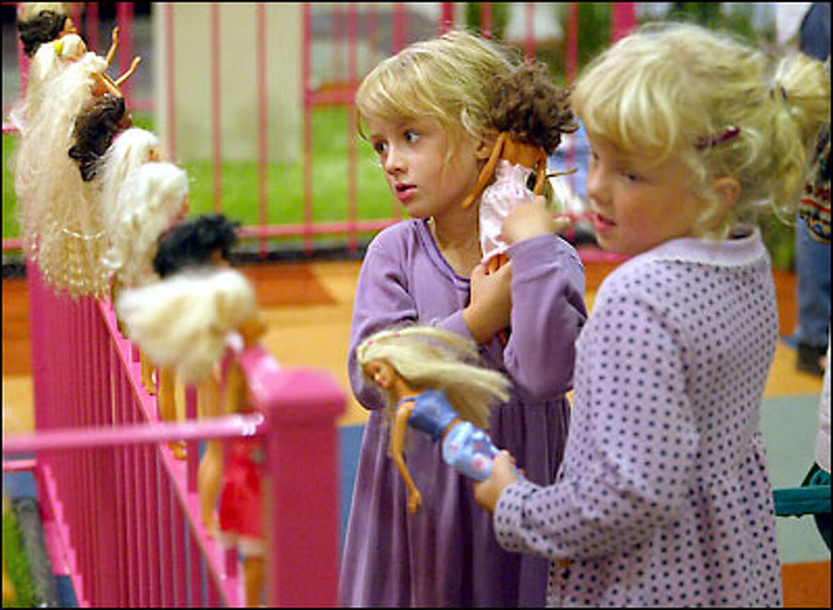 Maddie Barnett, left, and Annalisa Brinchmann, both 5, of Seattle brought their own Barbie dolls to the Barbie@Bumbershoot exhibit yesterday.