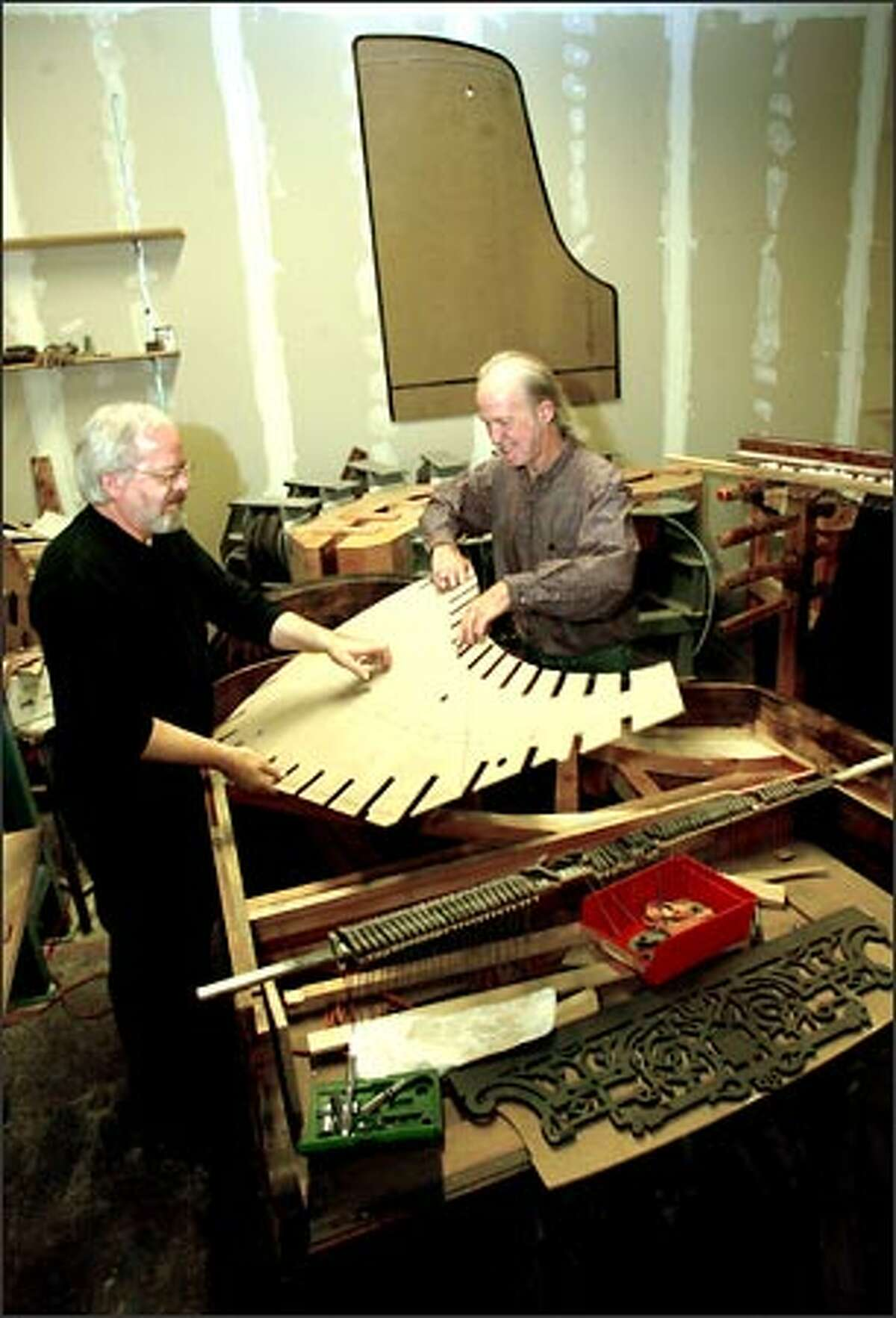 Fandrich, left, and business partner Larry Graddy position a soundboard template into an 1889 Decker piano they are remanufacturing at their PianoBuilders NW shop in Hoquiam. Fandrich often will rebuild old pianos in new ways.