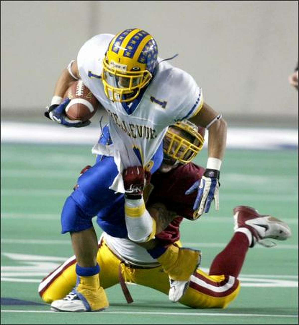 O'Dea's Anthony Felder, on ground, brings down Bellevue's Tracy Ford in the 2003 3A title game.
