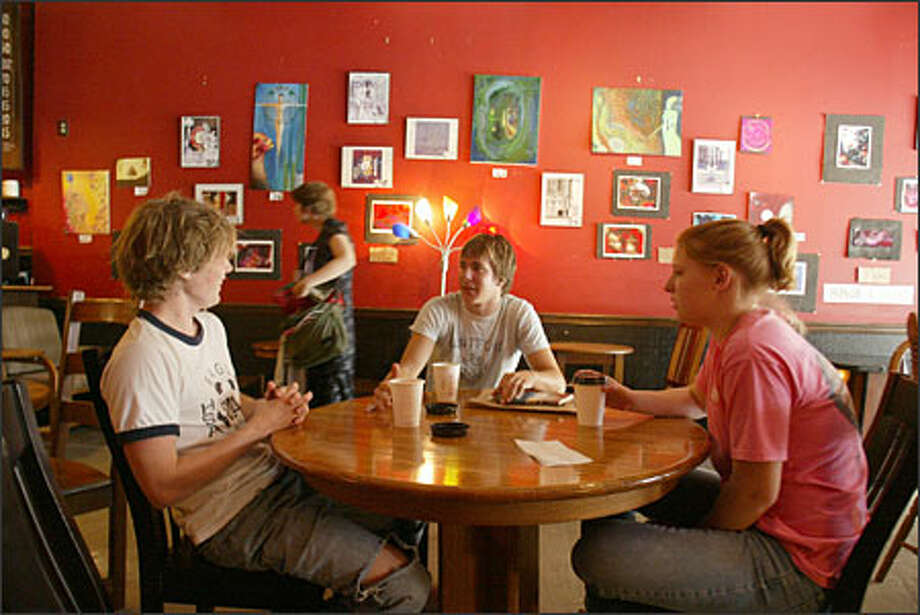 It ain't Starbucks: Sureshot's blood-red walls and cavelike lighting is hipster, not upscale. The shop attracts a wide range of customers, including Jonathan Brown, left, Matt Clark and Melissa Clark. Photo: Phil H. Webber, Seattle Post-Intelligencer / Seattle Post-Intelligencer