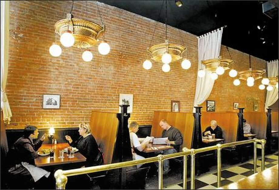 Lunchtime at The Belltown is casual and ideal for conversation. The exposed brick walls, unusual light fixtures and high-backed smooth wood booths provide an attractive setting. Photo: Meryl Schenker, Seattle Post-Intelligencer / Seattle Post-Intelligencer