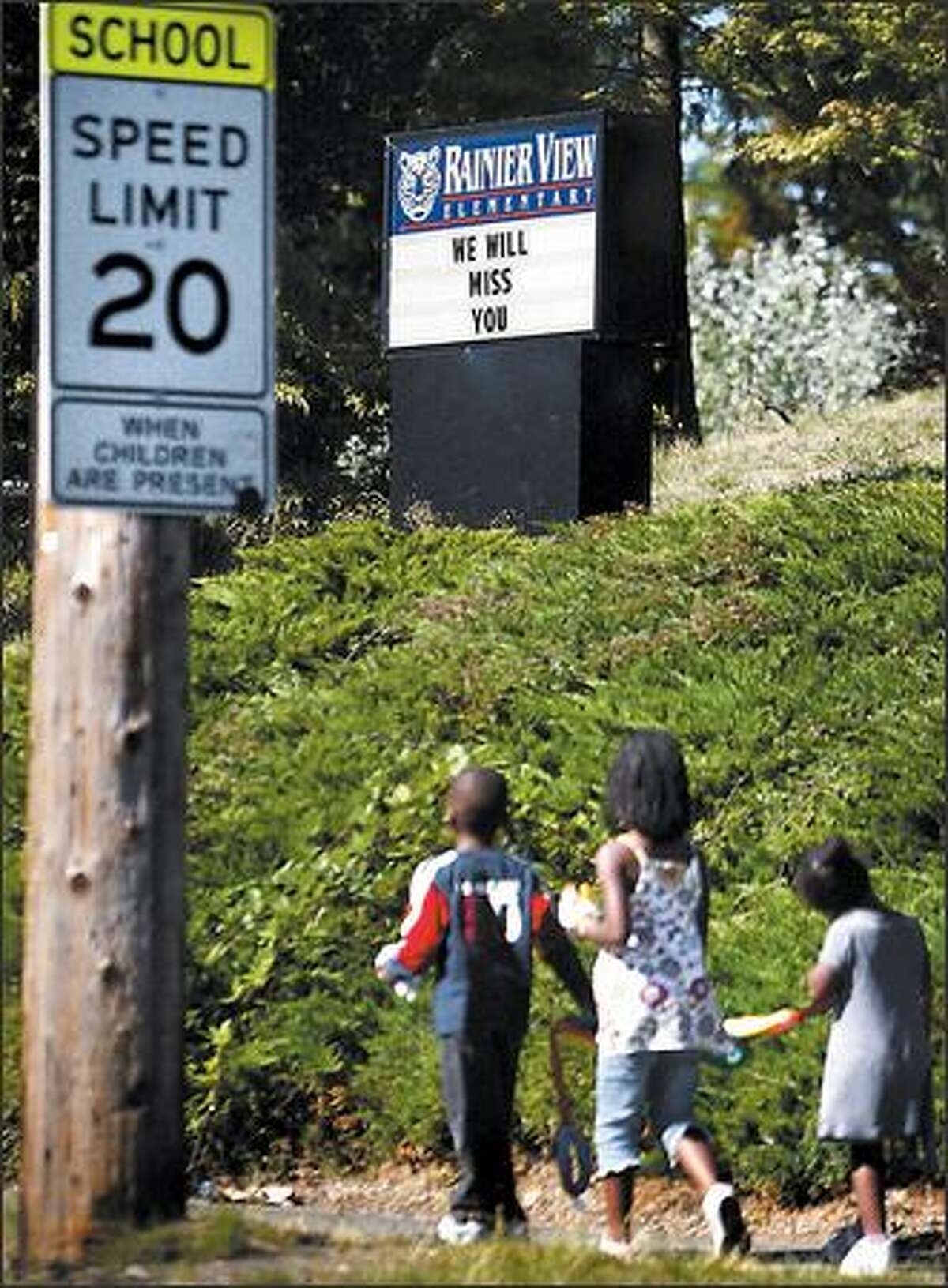 Children walk by Rainier View Elementary on Thursday. Neighbors worry the closed school could become a magnet for crime.