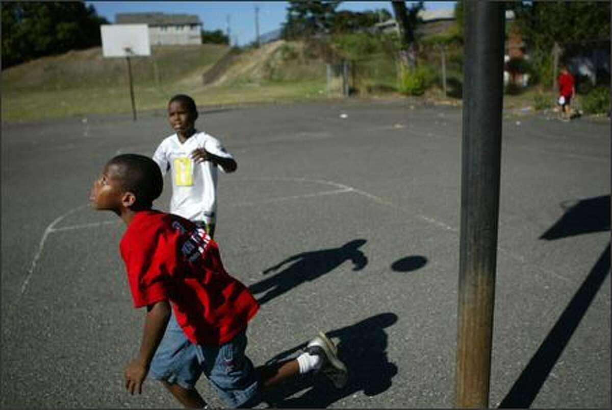 Isaiah Shallow, 10, left, and his brother Jeremiah, 9, shoot hoops at the recently closed Rainier View Elementary on Thursday. The boys think it's a good idea to turn the empty school into a community center.