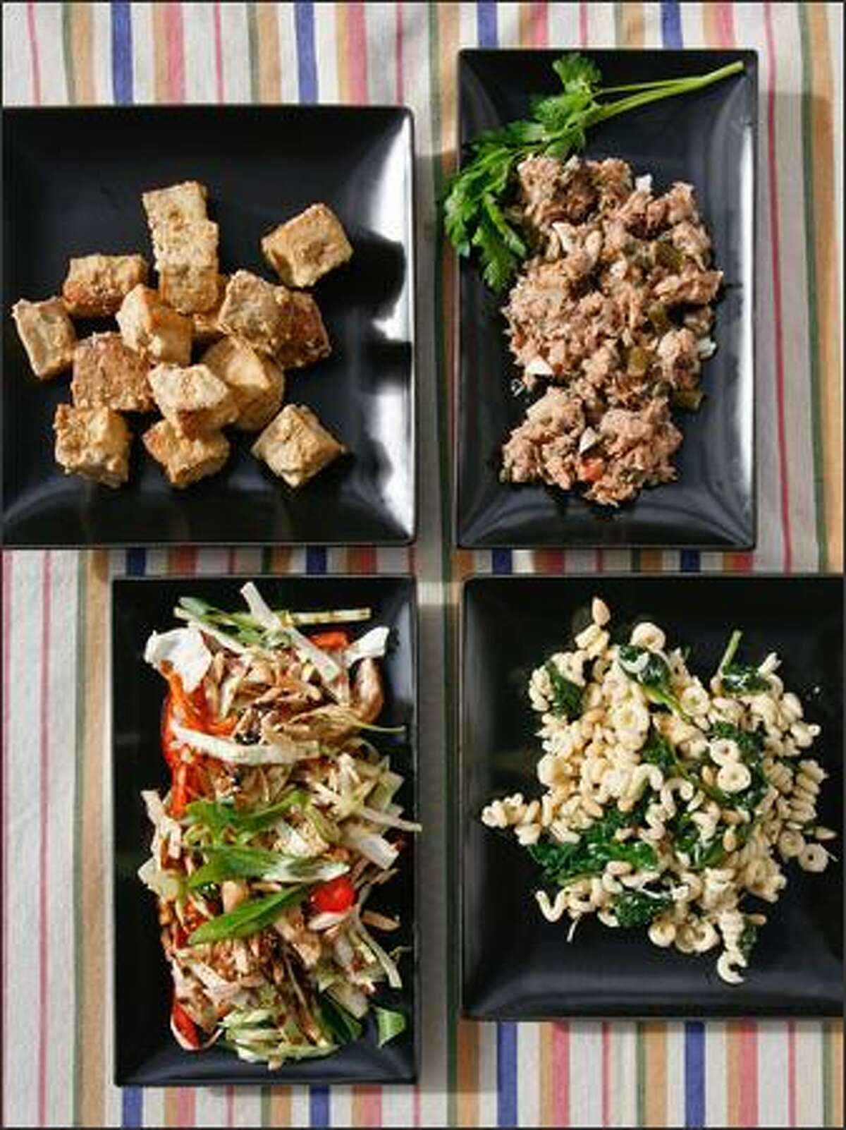 Clockwise from upper left: Steph's Tofu from PCC Natural Markets, Italian Tuna Nicoise Salad from Metropolitan Markets, Spinach Pasta Salad from Top Foods, and Ginger Chicken Cabbage Salad from Pasta & Co.