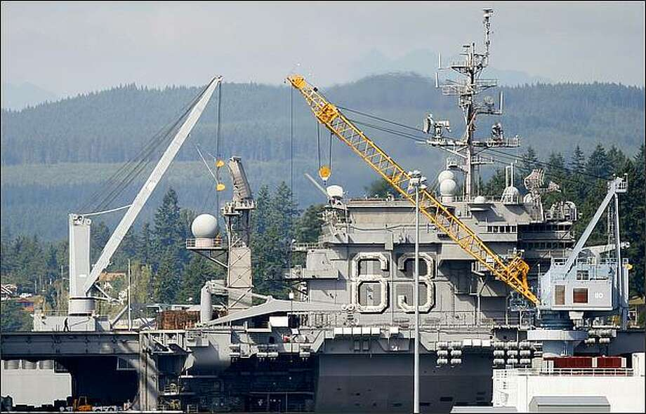 The USS Kitty Hawk, the Navy's last diesel-powered aircraft carrier, arrives at the Puget Sound Naval Shipyard in Bremerton for decommissioning.  The Attorney General's office, environmental groups and the Suquamish Tribe worry that the Navy will scrape its hull and release contaminated solids into Sinclar Inlet.  Photo: Joshua Trujillo, Seattlepi.com / seattlepi.com