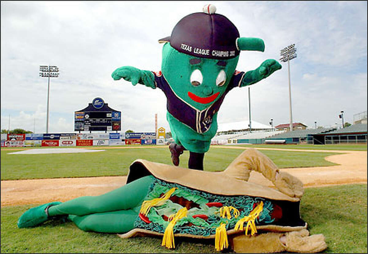 Puffy Taco, named the best mascot in minor-league baseball, is about to get crunched by co-worker Ballapeno as part of their routine at a San Antonio Missions game.