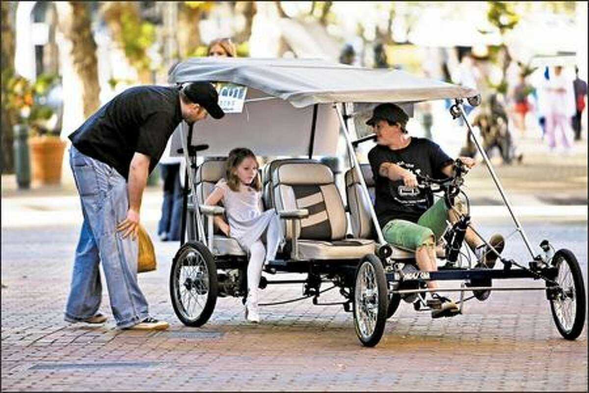 Candi Wilvang talks to Mitch Brausky and his daughter, Jocelyn, 5, as they board her four-wheel pedicab in Pioneer Square for a ride to Qwest Field.