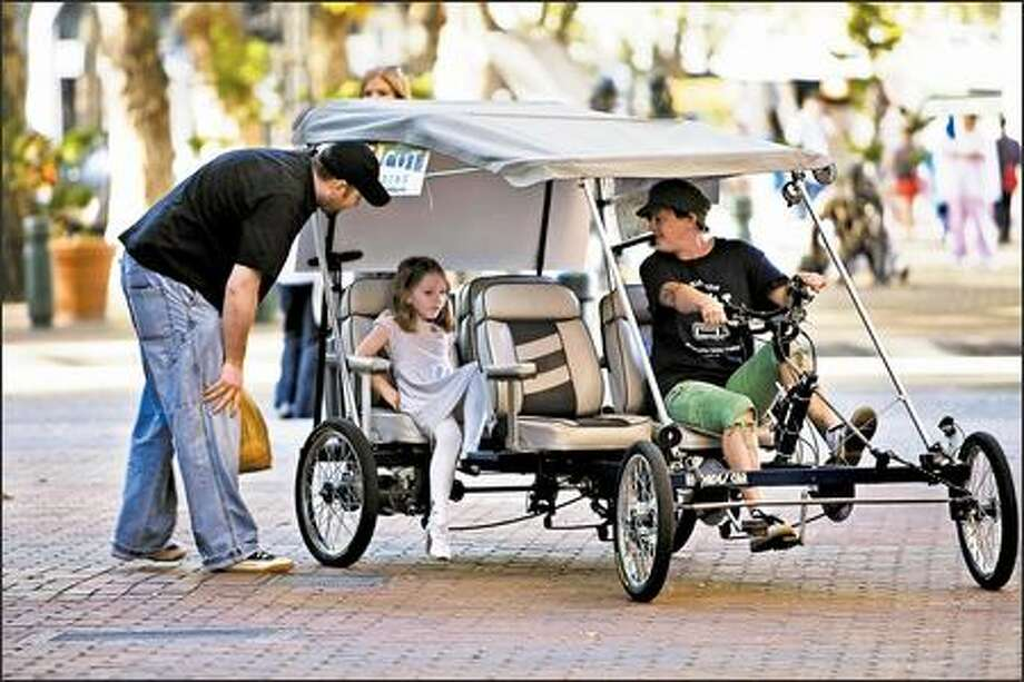 Candi Wilvang talks to Mitch Brausky and his daughter, Jocelyn, 5, as they board her four-wheel pedicab in Pioneer Square for a ride to Qwest Field. Photo: Grant M. Haller, Seattle Post-Intelligencer / Seattle Post-Intelligencer