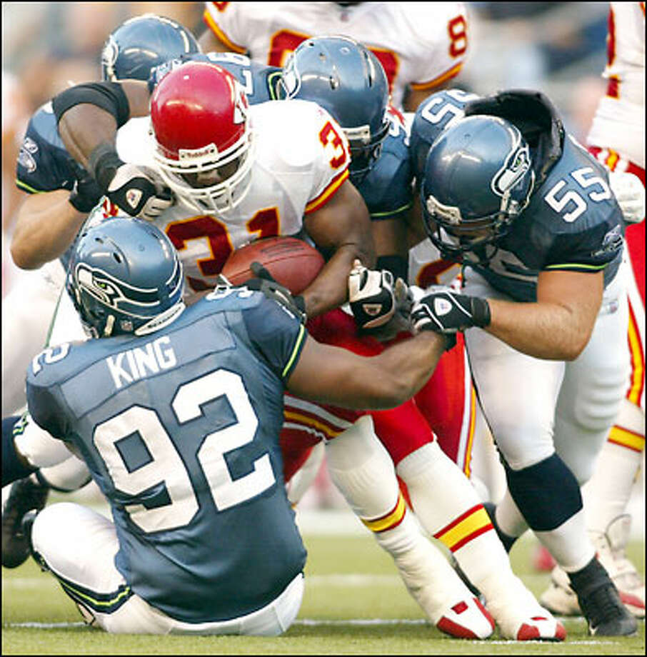 Lamar King stops the Chiefs' Priest Holmes with help from Marcus Bell (55) and Brandon Mitchell (97) in the Seahawks' lone preseason win. Photo: Associated Press / Associated Press