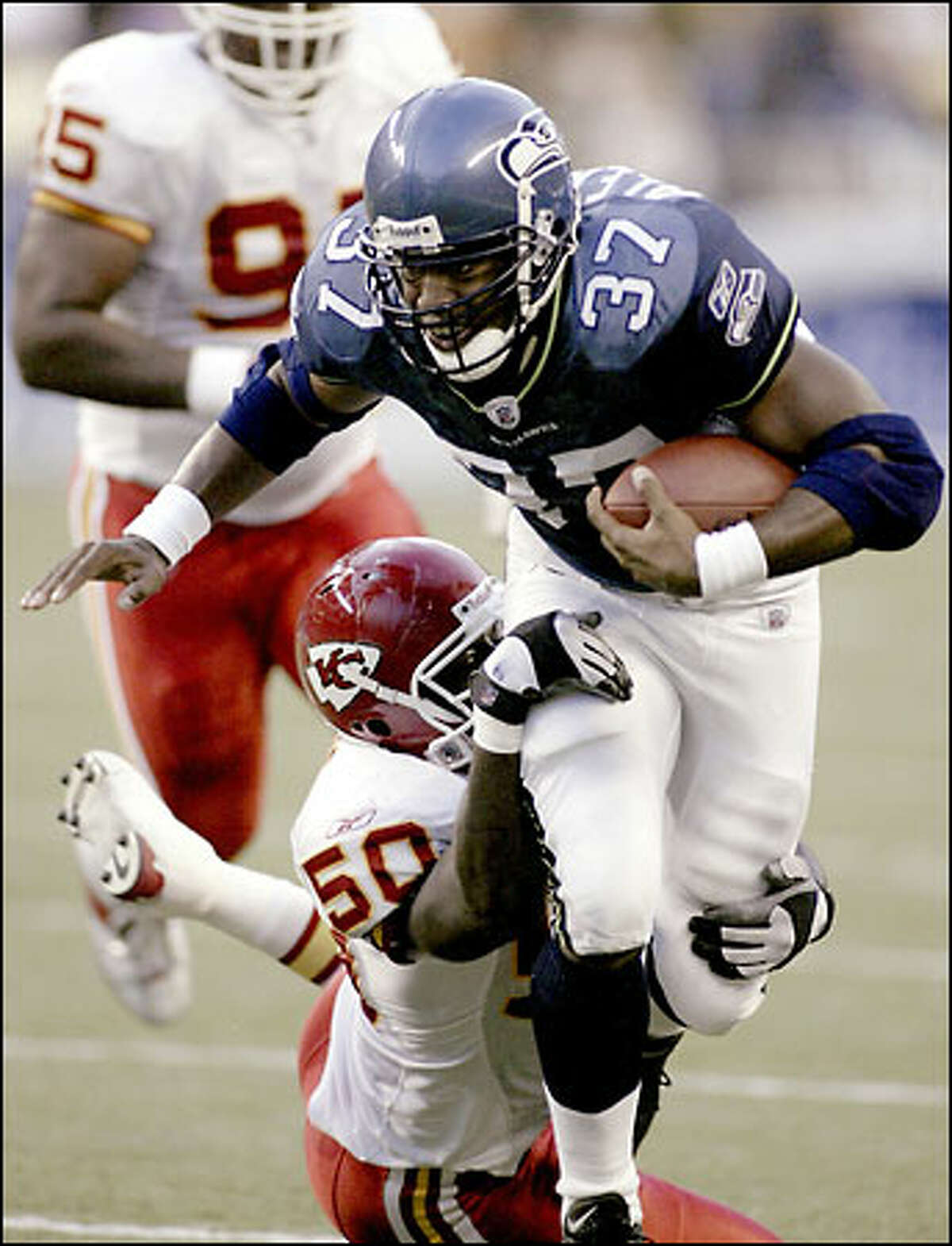 Shaun Alexander carries Chiefs linebacker Larry Atkins for extra yards during the Aug. 24 game at Seahawks Stadium.