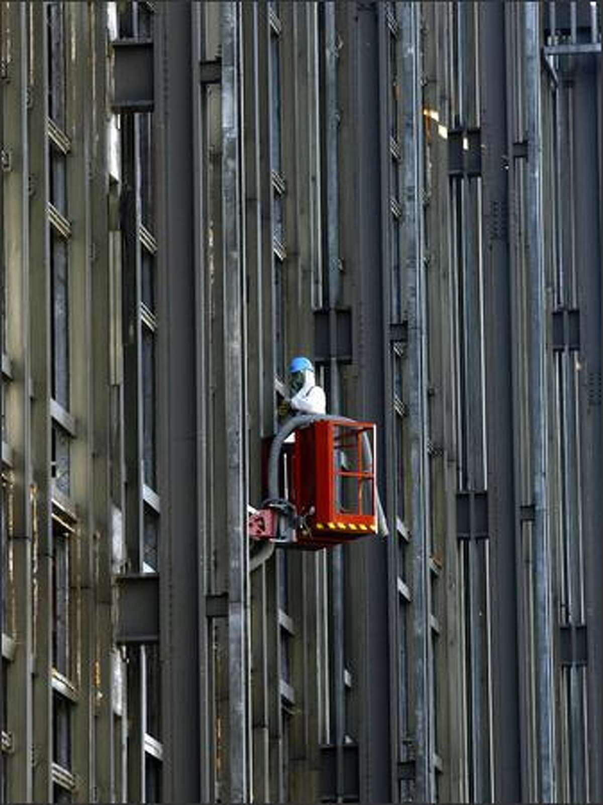 A man works at the steel facade of the former Palace of the Republic, the parliament building of former East Germany, in Berlin. The former parliament building will be demolished and work is expected to continue until December 2008. (AP Photo/Markus Schreiber)
