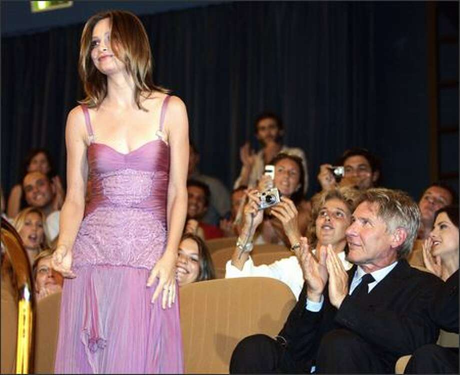"Harrison Ford joins the Venice Film Festival audience in its appreciation of former ""Ally McBeal"" star Calista Flockhart, whose latest film, ""Fragile,"" screened last week. Harrison, we like her too. And we're glad to see that she doesn't look as though she's starving anymore. Photo: Associated Press / Associated Press"