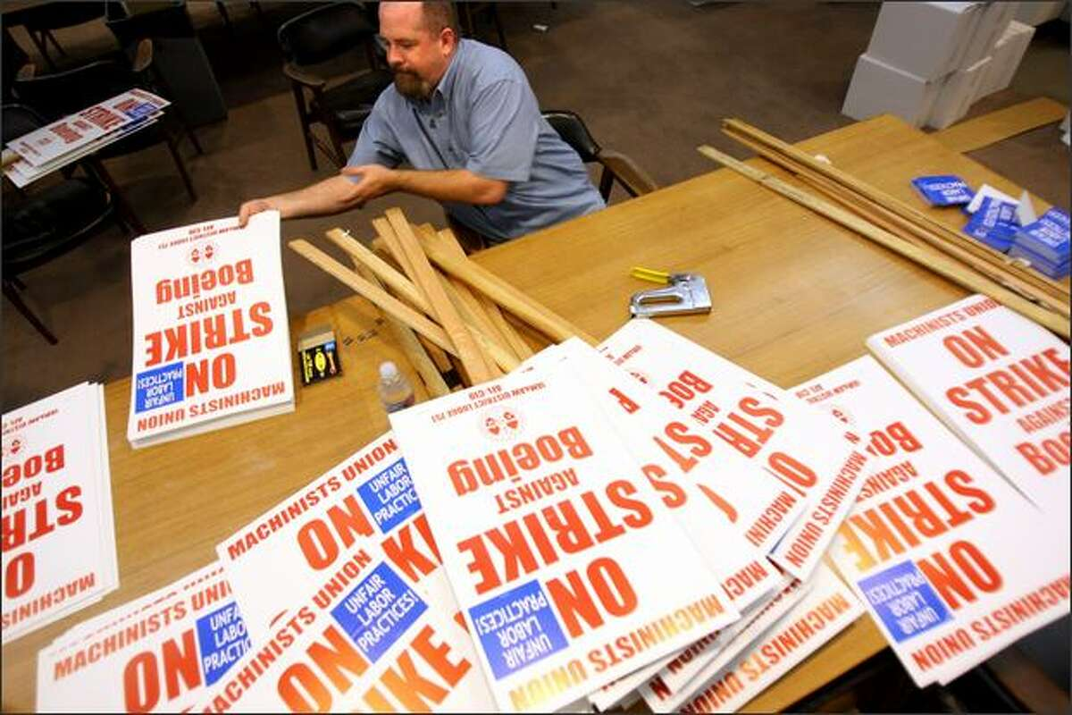 IAM & AW District 751 IT worker Ken Finlayson constructs strike signs at the Tukwila union hall after the announcement was made for union workers to strike at midnight Frida.