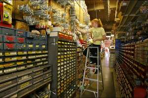 Maribeth Hardwick, the daughter of co-owner Bill Hardwick, stocks the shelves at the family-run hardware store Hardwick's Swap Shop in the University District.