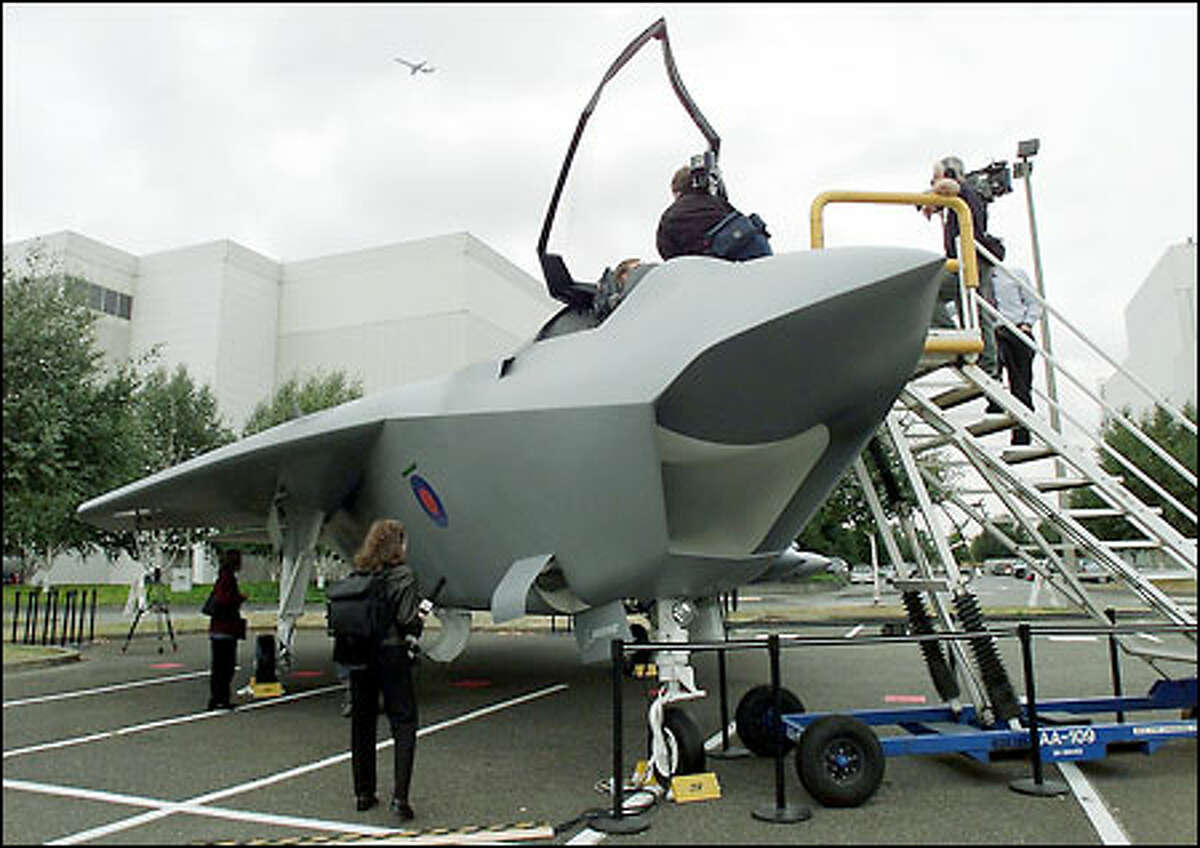 Members of the news media view a mock-up of Boeing's Joint Strike Fighter at the Developmental Center across from Boeing Field.