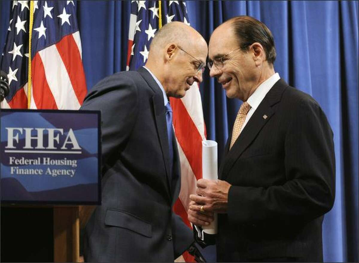 Treasury Secretary Henry Paulson, Jr., left, and Federal Housing Finance Agency Director James Lockhart, right, exchanges places during their news conference in Washington, D.C., on Sunday on the bailout of mortgage giants Fannie Mae and Freddie Mac.