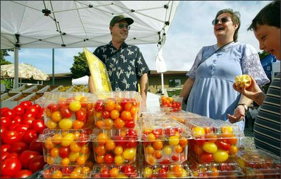 """Lisa Baxter and son Jeffrey experience what Wade Bennett calls the """"wow"""" factor as they try one of his apples at the Burien farmers market. Photo: Paul Joseph Brown, Seattle Post-Intelligencer / Seattle Post-Intelligencer"""