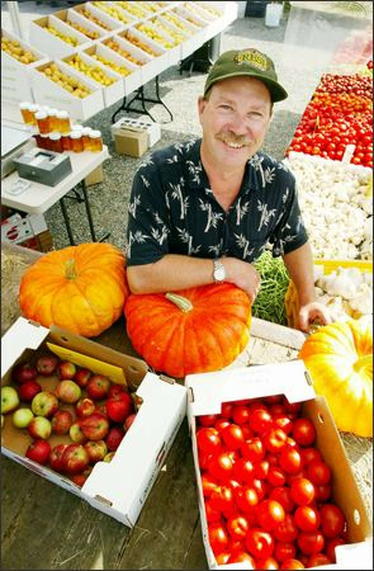 Wade Bennett's stand at the Burien farmers market is filled with vegetables and fruits from his Rockridge Orchards in Enumclaw. His diverse 41-acre orchard produces 160 different items.