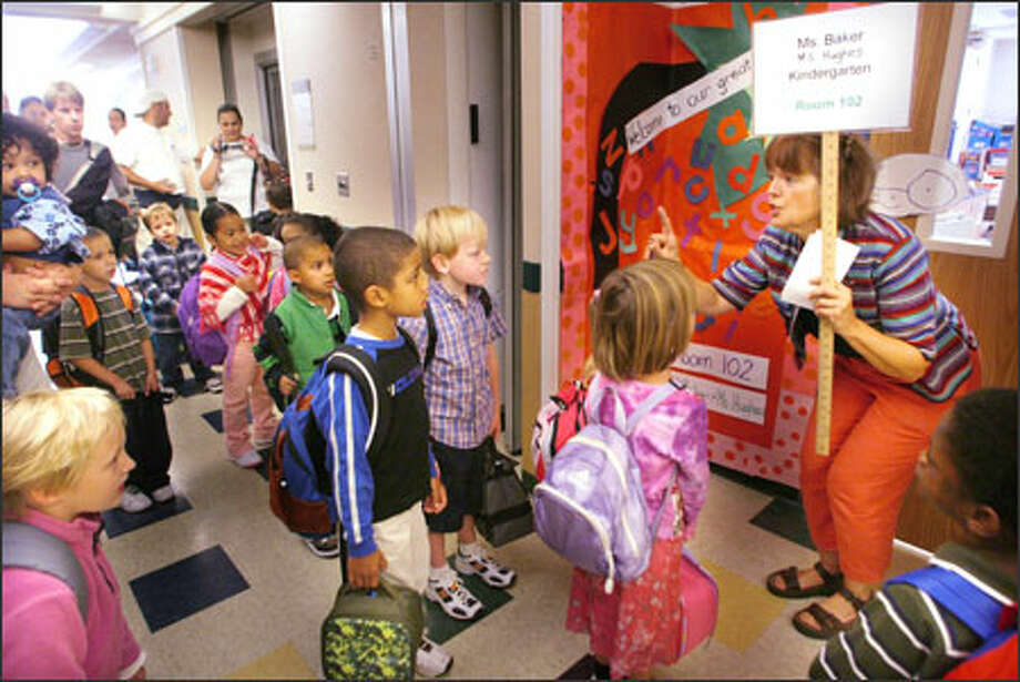 On the first day of school, Kas Baker of Greenwood Elementary School tells her kindergarten class that they should find their names and sit in that seat. Photo: Karen Ducey, Seattle Post-Intelligencer / Seattle Post-Intelligencer