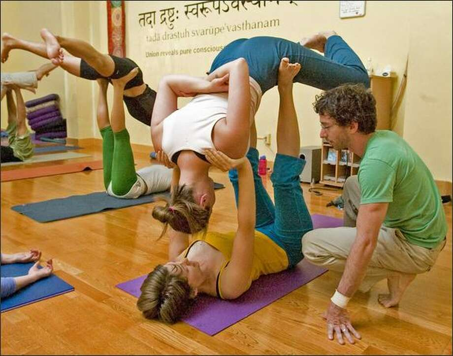 Instructor Lux, right, works with Erica Stephens, lower, and Joanna Guyette during an acro yoga class on Capitol Hill. Photo: Grant M. Haller, Seattle Post-Intelligencer / Seattle Post-Intelligencer