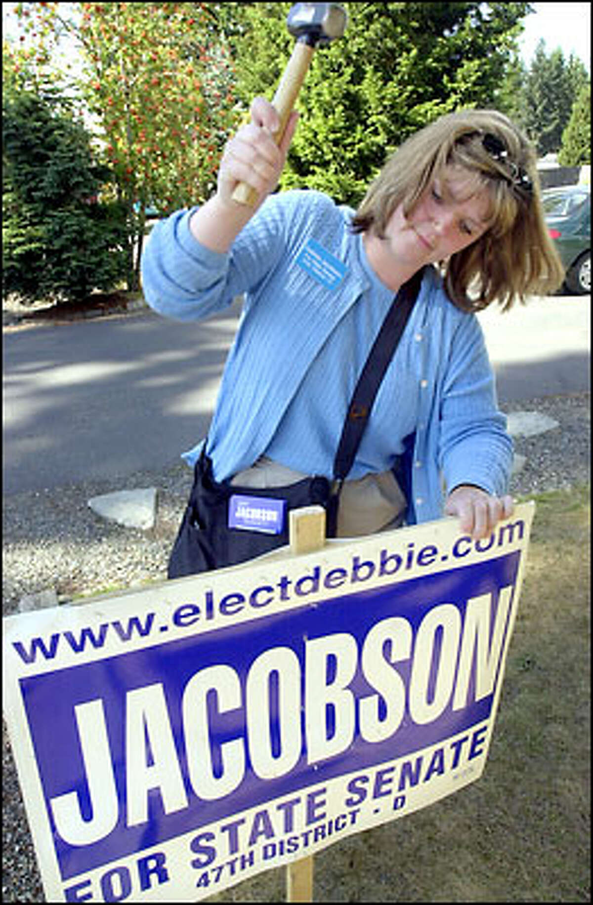 South King County Democrat Debbie Jacobson pounds in a campaign sign in the yard of a supporter in Covington, last Thursday.