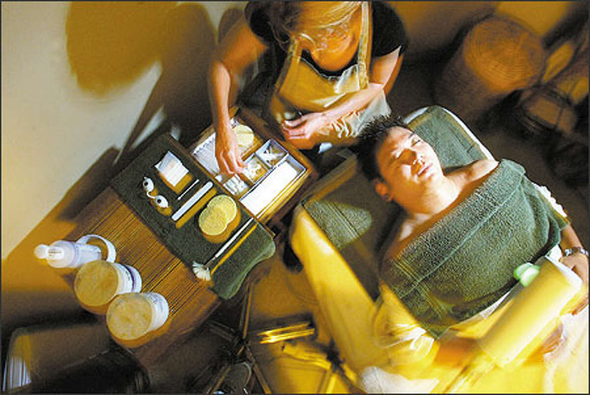 """Tess Martinovic of Ummelina International Day Spa gives a facial to Jon Ima of Seattle, a regular client. """"It's kind of like a mini-vacation. It takes the stress away,"""" said Ima."""