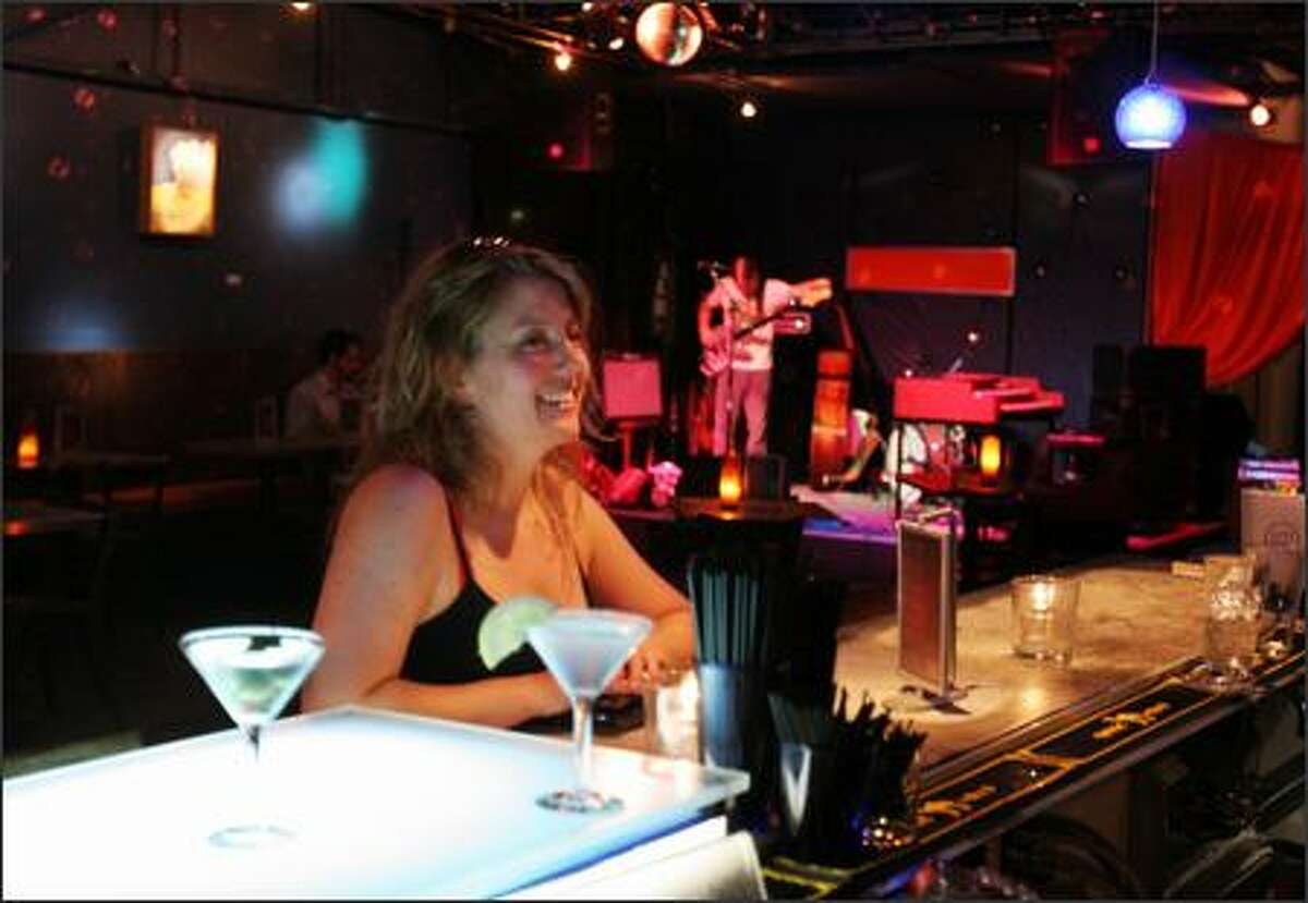 Kate Sykes of Seattle waits for her mango cosmopolitan at Tost Lounge in Fremont, while musician Jon Markel gets his bass in gear. Watch for Tost's new owners to revamp what is, for now, a menu of mostly mediocre salads, sandwiches and pizzas.