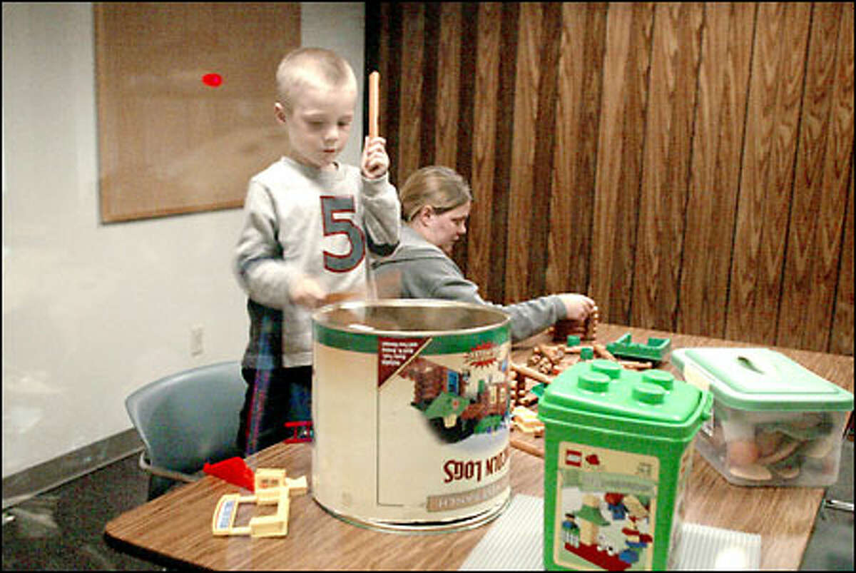 Levi Walker responds to the announcement that playtime is over by banging on the metal bottom of the Lincoln Logs container. His mother, Jodi, is coached to turn her back and say out loud how much fun she's having playing alone. At first his angry drumming drowns out his mother's voice.