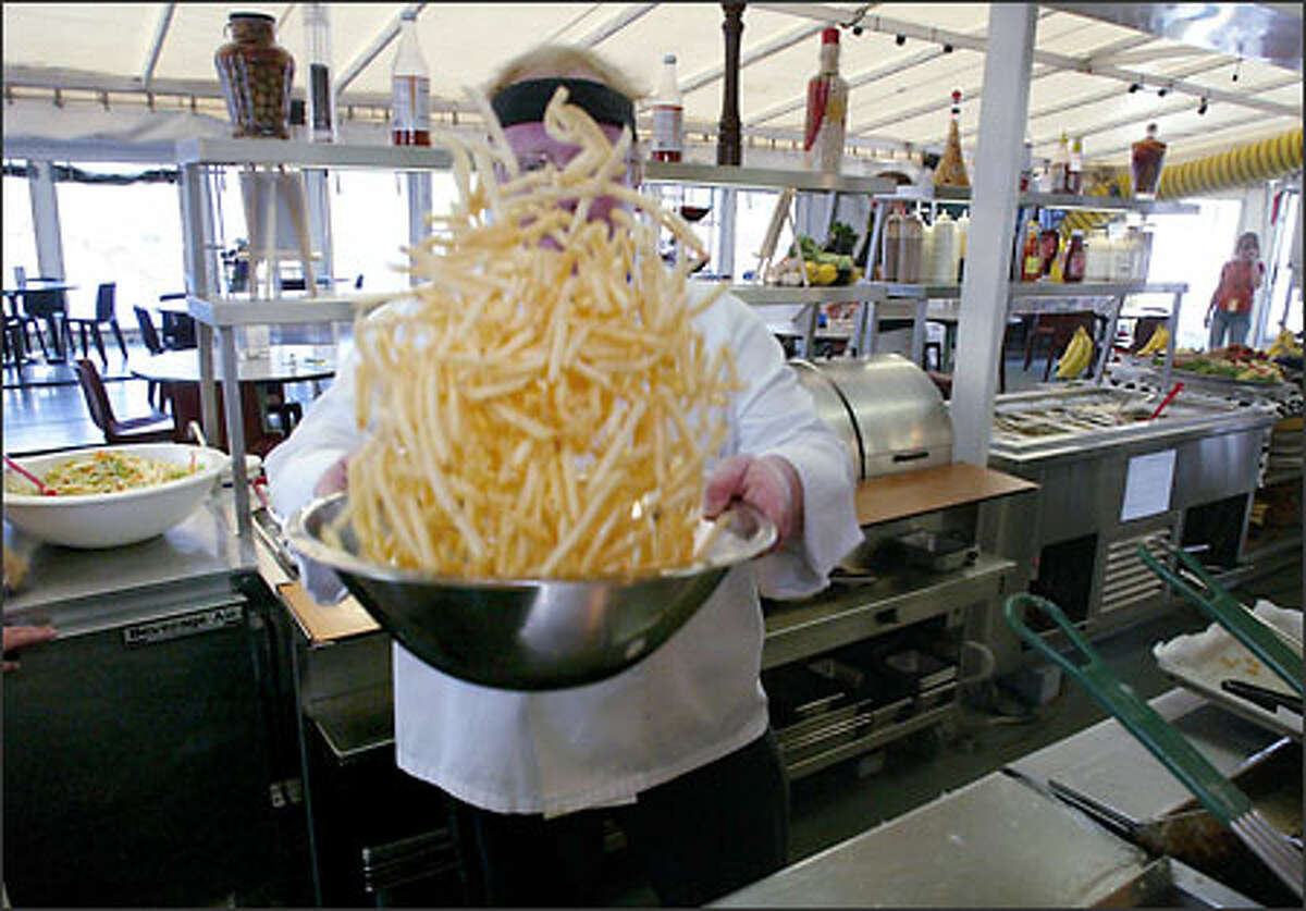 Chef Nick Westley, who was born in England, tosses a bowl of fries while preparing cod fish and chips. One day a week is designated fry day, otherwise,