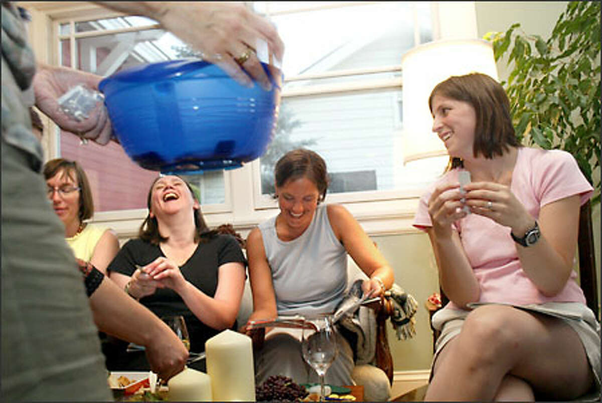 """""""You want to make sure people have fun,"""" says Tupperware consultant Dana Miller, holding a Tupperware colander as partygoers check their raffle tickets for free gifts. From left are Barbara Spear, Sunny Delaney, Patty Moriarty and Amy Arnold."""