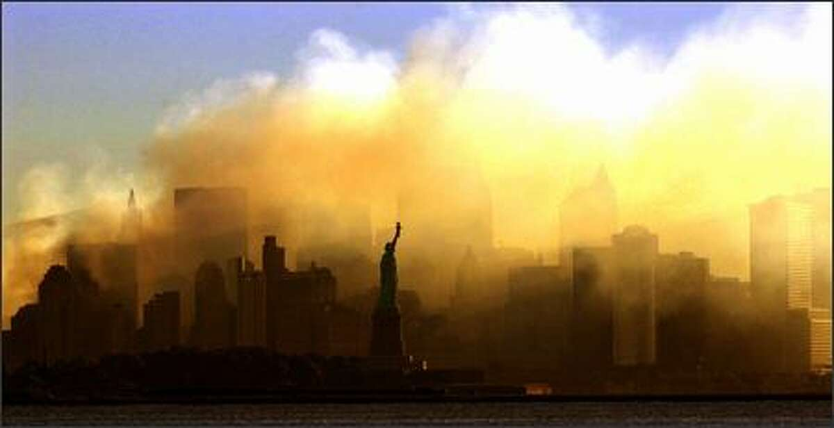 The Statue of Liberty can be seen at first light from a view from Jersey City, N.J., as the lower Manhattan skyline is seen though a thick smoke filled the sky early morning in this Sept. 15, 2001, file photo.