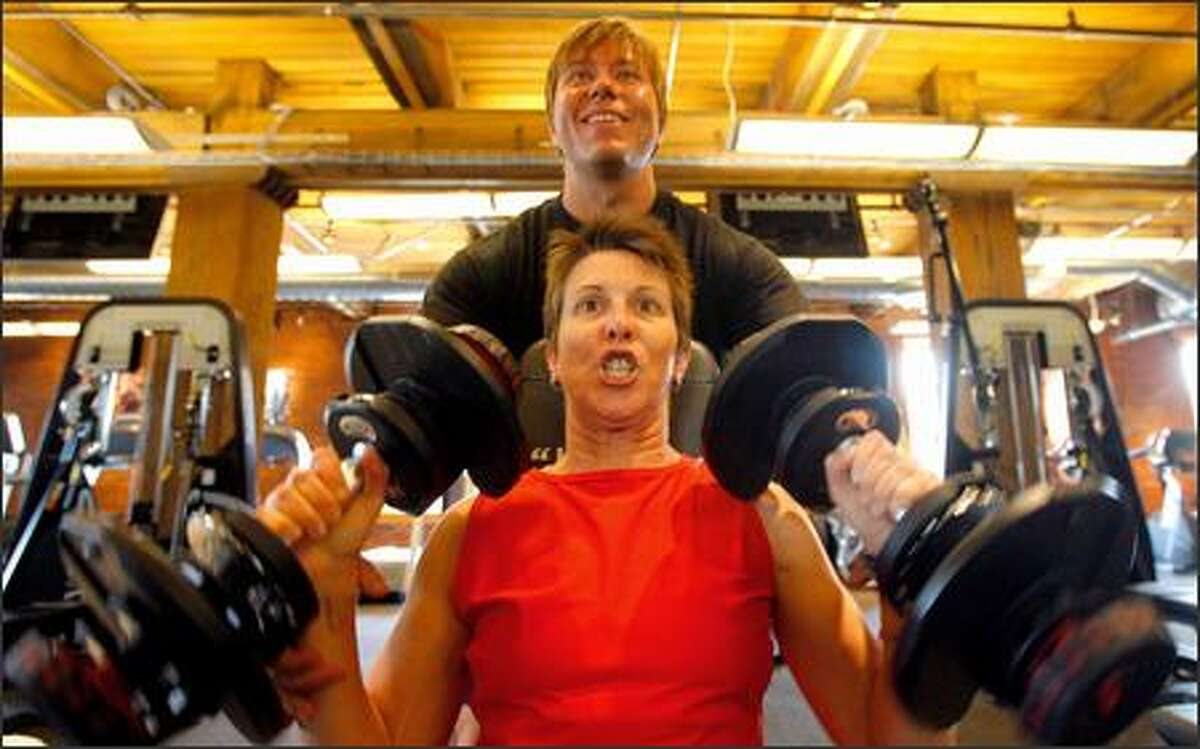 Starbucks' Nancy Haver pumps iron with the help of Jamie Brunner, co-founder of Kinetix Living. Haver says she's lost 30 pounds since starting the program.