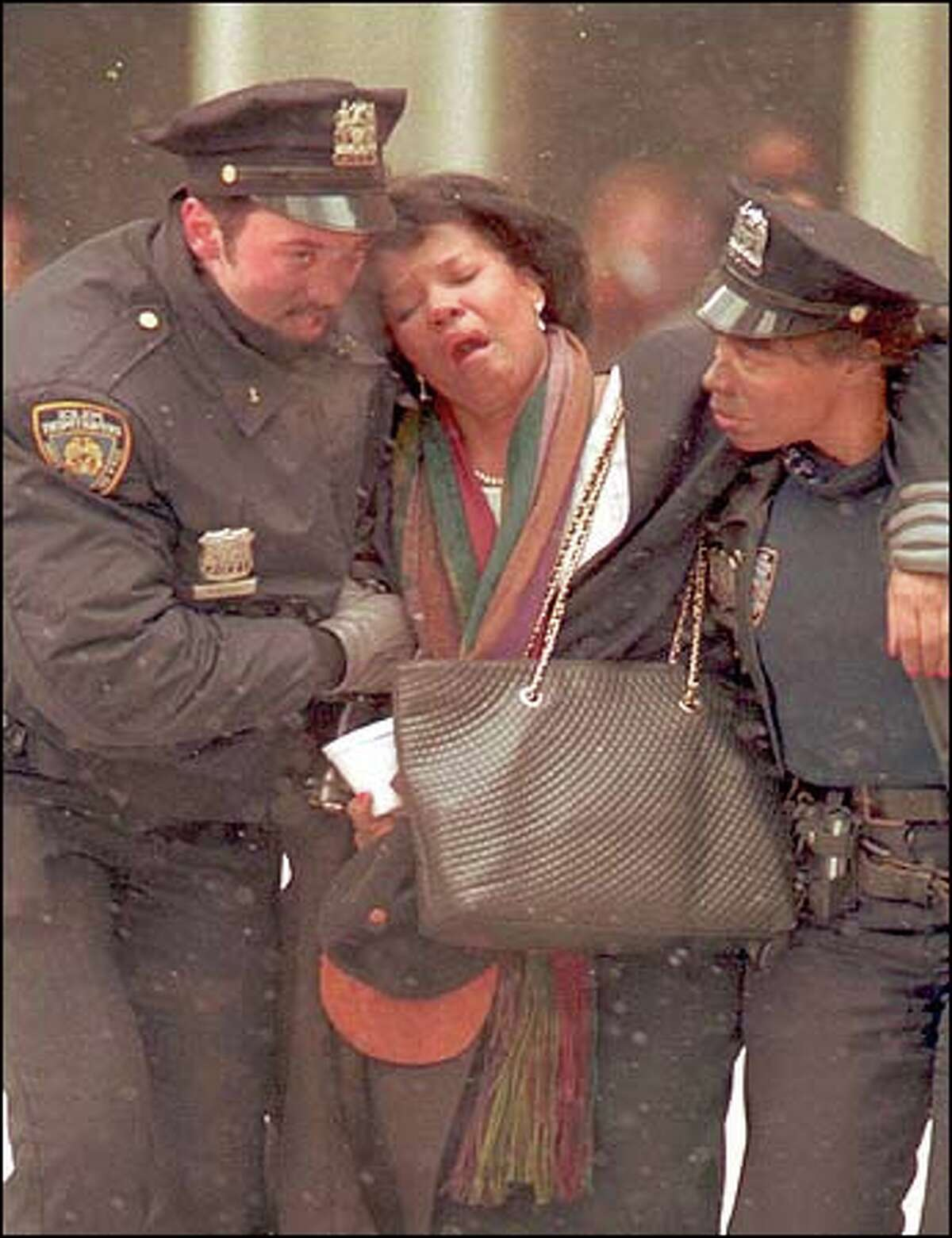 A woman is helped by New York City police outside of the demolished World Trade Center buildings Tuesday morning.