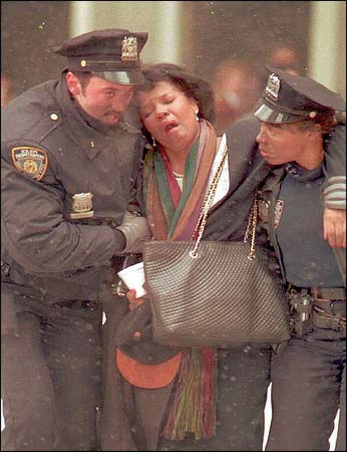 A woman is helped by New York City police outside of the demolished World Trade Center buildings Tuesday morning. Photo: Associated Press / Associated Press