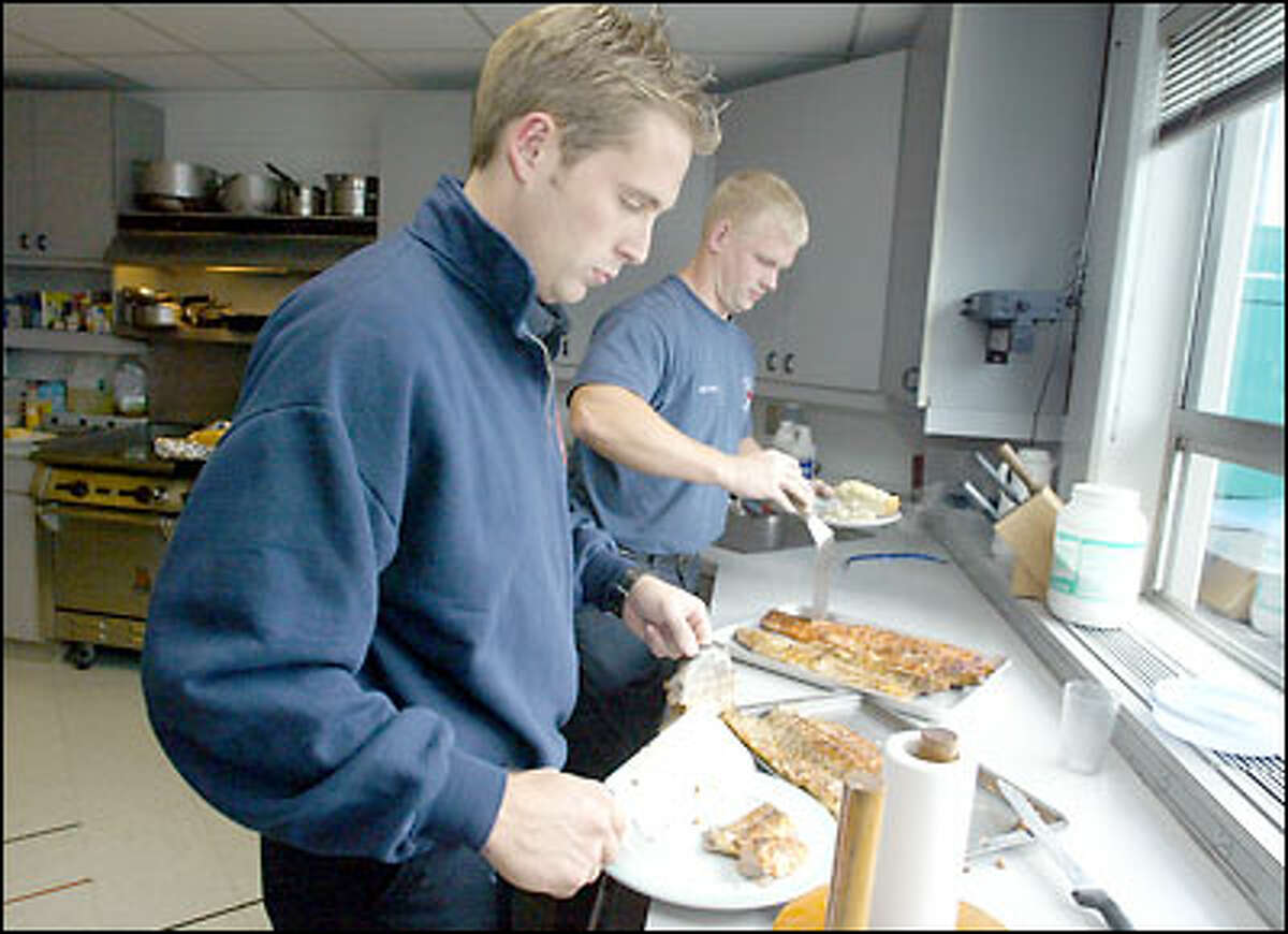 Station 5 firefighters Elijah Perez, left, and Gary Mitchell help themselves to some freshly grilled salmon, seasoned with a dry rub, that was prepared by fellow firefighter Tom Nelson.