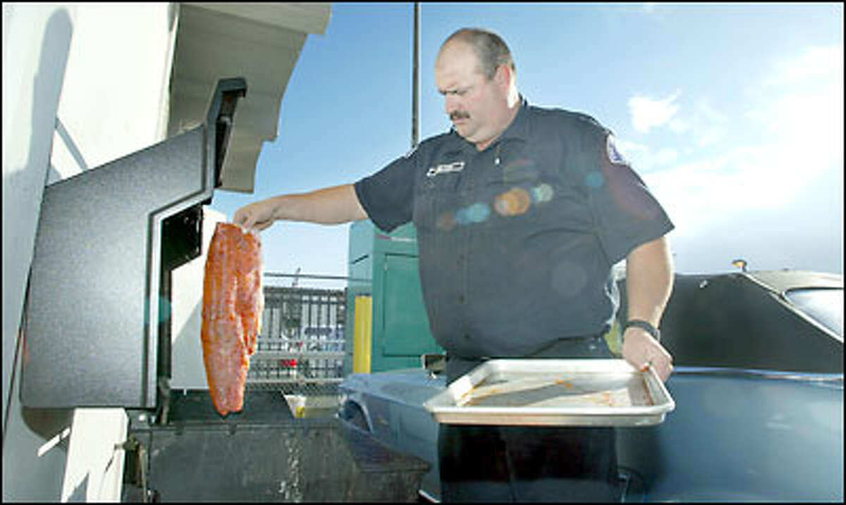Seattle firefighter Tom Nelson grills up fresh salmon for the team at Station 5. Nelson, who's also a fishing guide, usually whips up fresh seafood dinners when he's on cook duty.