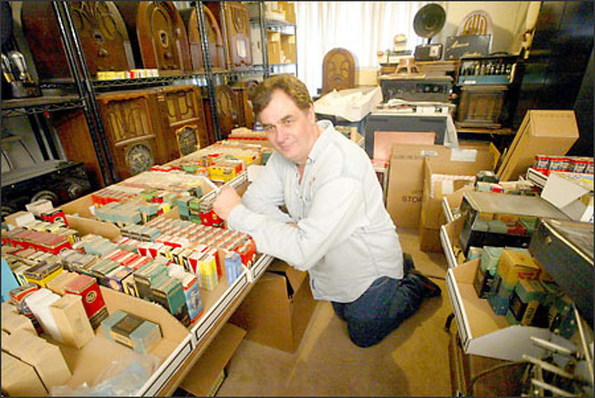 Nigel Featherston in the living room of his Redmond home with his collection of old radios and radio tubes.