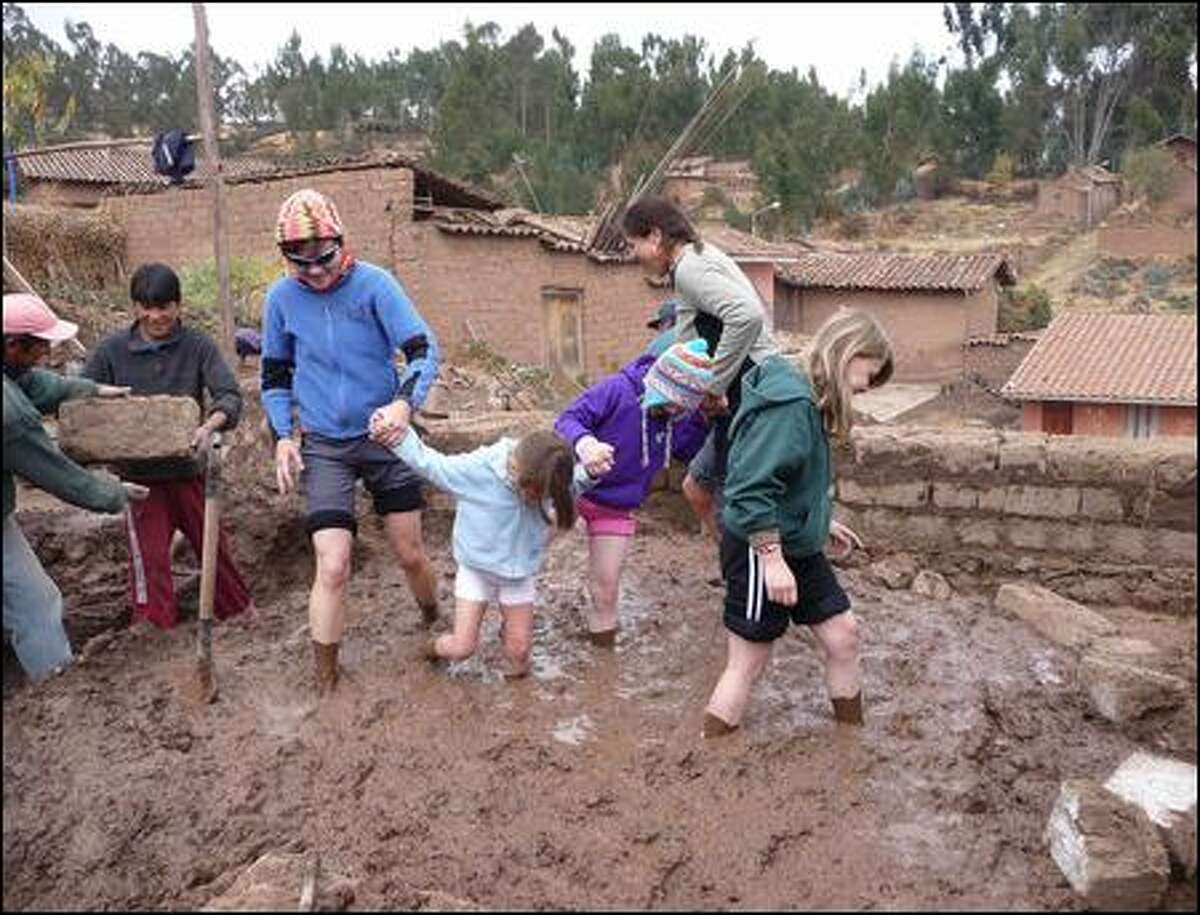 Doing their muddy best to make mortar for an orphange in Chinchero, Peru, are, from left, Sarah Mackay of Seattle, Trinity Mackay and her mom, Chris Mackay, of Seattle (no relation to Sarah), and twin sisters Alison (in hat) and Megan Heatherington of Redmond. Seattle-based Crooked Trails annually offers tours to Peru, Ghana, Nepal and other destinations. (Crooked Trails)