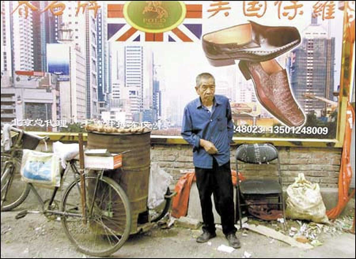 A man who sells baked sweet potatoes stands below a billboard at a shoe market in Beijing that promotes footwear imported from the United States.