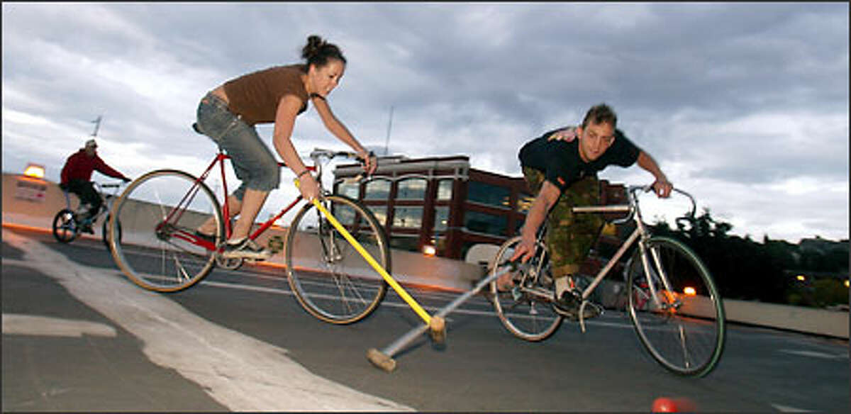 Bike messengers Kayt Bamford and Guy Bagley polish their polo skills in a parking lot atop a condemned building in the South Lake Union area. Polo is new to the World Cycle Messenger Championships, which start today and run through Sunday.