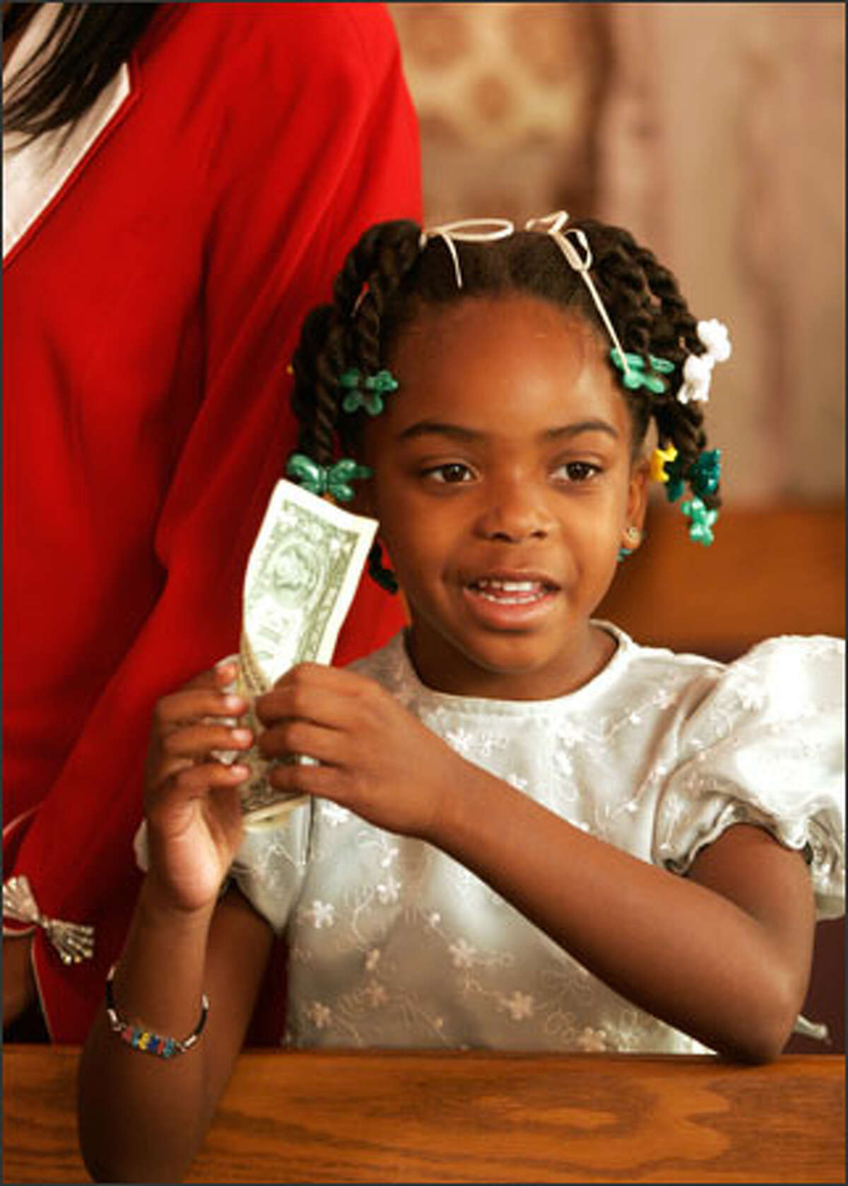 Alexis Rogers, 6, holds a dollar for a tithe during Sunday's service at the Unity Church of God in Christ. The church also was raising money to help with the Katrina relief effort in the South.