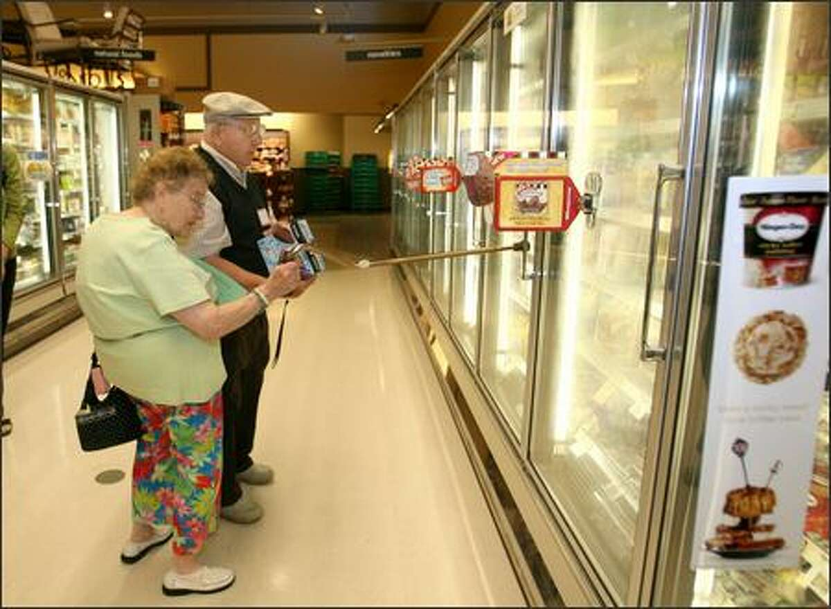 """Shoppers Rose and Isacc Motola check out frozen desserts at the Rainier Valley Safeway. King County Public Health sponsors a """"shop around"""" at the Safeway every Monday, where they have a """"peer educator"""" who helps educate folks about nutrition labels and healthier food."""