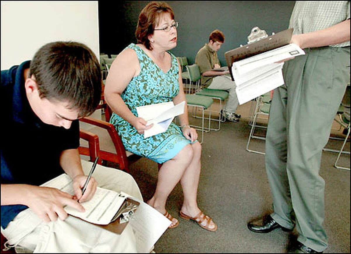 Debbie Goltiani of Renton brought her son, Tim, left, and his friend, Brad Hinton, showing her his application, to the REI job fair in Kent yesterday.