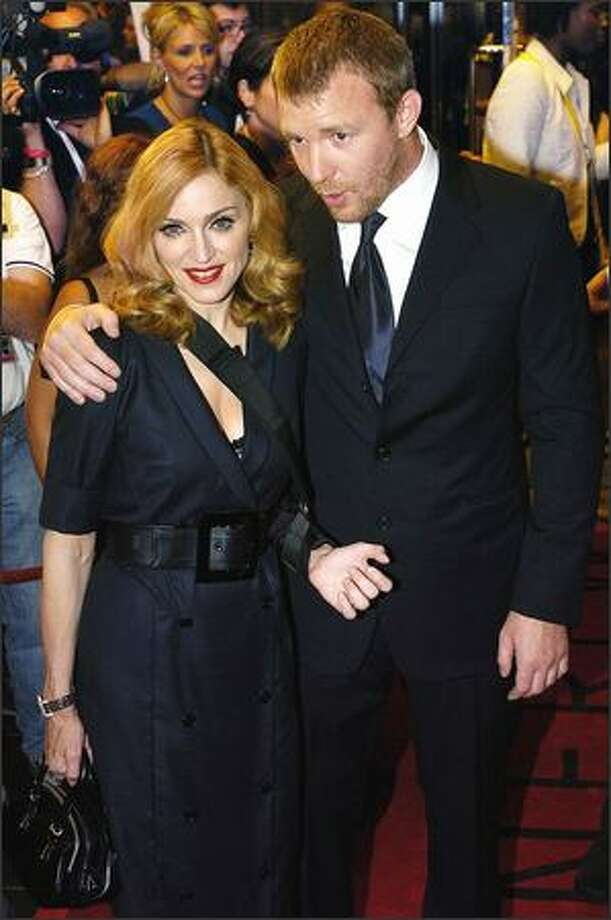 "Madonna works it for the camera while arriving at the Toronto International Film Festival with hubby Guy Ritchie on Sunday. They were promoting his new film, ""Revolver,"" a gambling and vendetta movie starring David Strathairn. If it's typical Ritchie fare, expect a lot of guns and plenty of violence. Photo: Associated Press / Associated Press"