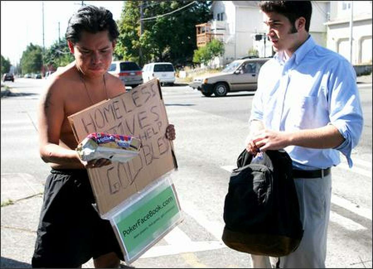 Zack Peters, left, who stood in the University District recently asking for help from passing motorists, received a package of Fig Newtons, $5 and bottled water from Ben Rogovy for holding a sign advertising Rogovy's Internet site. Rogovy's practice of using beggars to advertise has sparked praise and criticism.